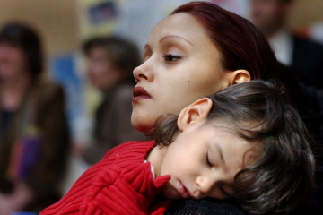 Adria Roman, 18, of Boston, and her son, Diano Perez, 3, both part of the Just A Start House program, attend a rally at the Statehouse in Boston, Tuesday, March 11, 2003, to protest budget cuts to shelter beds for homeless young families and to support the continuation of programs to help educate young mothers and teen pregnancy prevention. (AP Photo/Patricia McDonnell)
