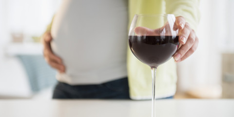 Pregnant woman with glass of red wine