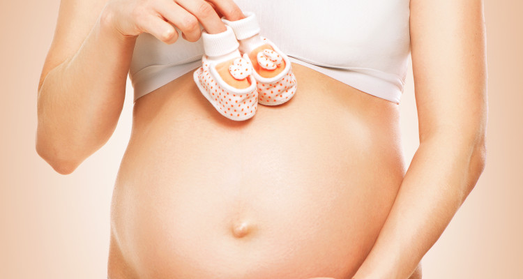 Pregnant Woman Belly. Pregnancy concept. Close-up of a Pregnant Woman holding Baby Shoes in her Hands. Mom Expecting Baby. Baby Shower